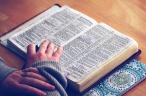 Odprt francoski slovar, malo popisan, punca ima na njem roko.