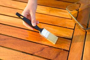 Nekdo s čopičem barva leseno mizo.