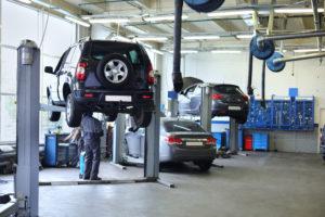 Avto je dvignjen na avtomobilski dvigalki sredi servisne garaže.